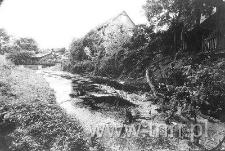 Drewniane, przedwojenne domy nad brzegiem rzeki