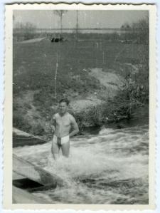Mężczyzna stojący w rzece przy moście