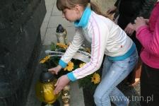 """Uczennica ze Szkoły Podstawowej nr 24 w Lublinie stawia znicz przed Pomnikiem Ofiar Getta - """"Listy do Henia"""" 2007"""